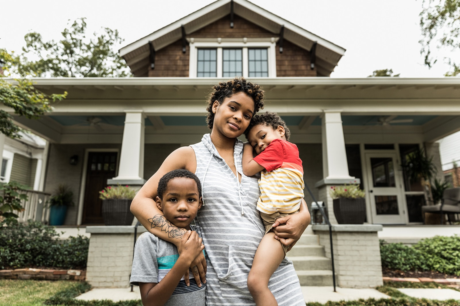 Woman with children in front of home
